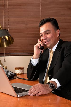 Hispanic executive having a phone conversation in his office. Stock Photo - 4893991