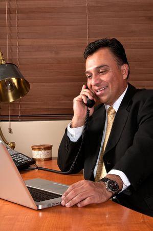 Hispanic executive having a phone conversation in his office. Stock Photo - 4893991