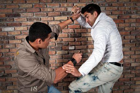 conflictos sociales: Chicos j�venes luchando en la calle con cuchillos. Foto de archivo