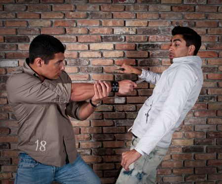 harassing: Young guys fighting in the street with knifes.