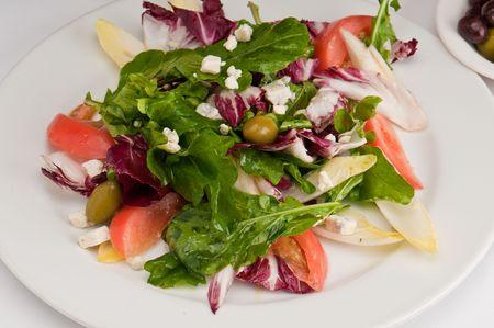 endive: Close up of salad made of arugula, radicchio, belgian endive, bibb lettuce, tomatoes, and olives.