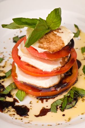 Salad of fresh mozzarella with vine-ripened tomatoes, pungent basil and extra virgin olive oil. photo