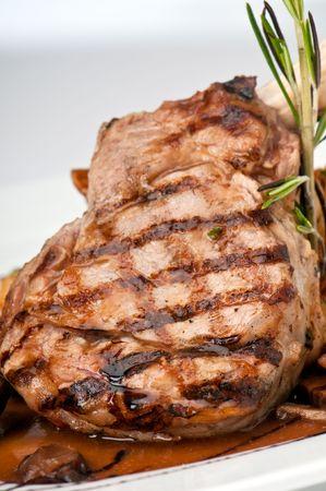 Broiled midden gesneden kalfsvlees hakken met gebakken uien en champignons. Stockfoto