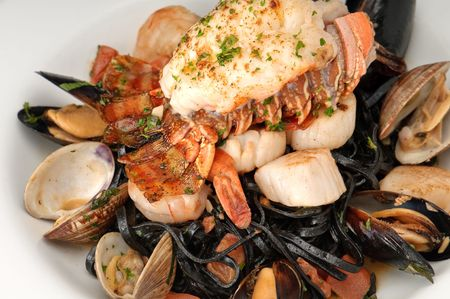jumbo shrimp: Plate of lobster served with sauteed jumbo shrimp, oysters and linguini pasta. Stock Photo