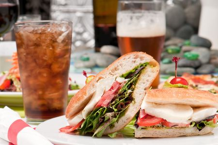 View of mozzarella and tomato sandwich with glass of soda in the background. photo