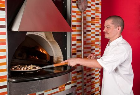 Young hispanic immigrant cooking pizza in a restaurant. photo