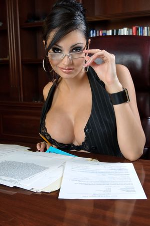 executive assistants: Beautiful and very sexy secretary working after hours. Stock Photo