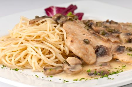 Plate of chicken picatta, lightly dredged in flour, sauteed in lemon, butter and white with fresh mushrooms and spaghetti pasta.