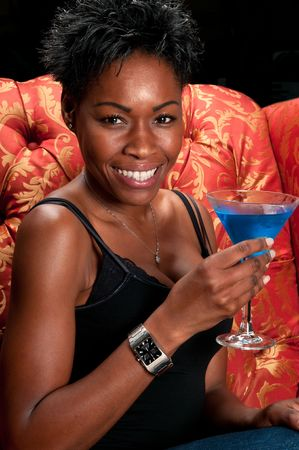 Young african american very happy having a blue martini cocktail in a restaurant. photo