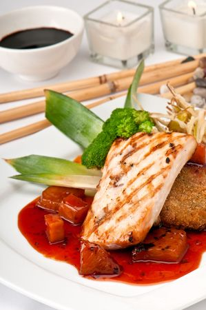 Plate of Mahi Mahi, severd with vegetables, pineapple and soy sauce. Stock Photo