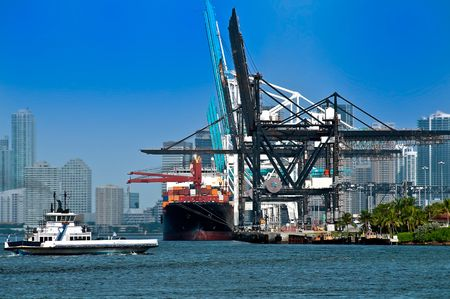 View of ferry boat and cargo ship in the Miami Seaport with the city in the background. Stock Photo