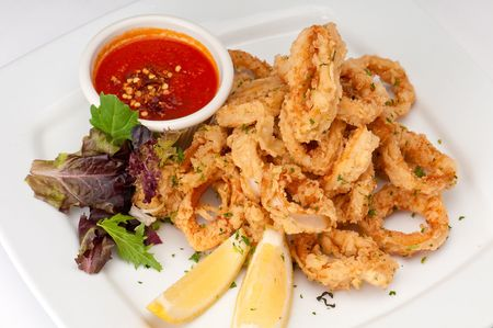 marinara: Plate of fried calamari served with marinara sauce and lemon. Stock Photo