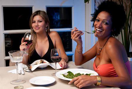 2 Jonge meisjes met diner in een restaurant. Stockfoto