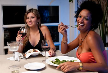 2 Young girls having dinner in a restaurant. photo