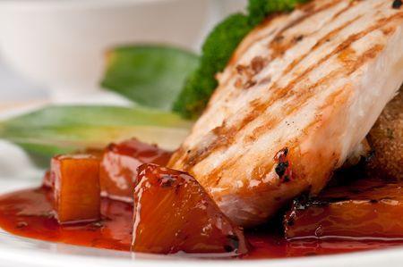 Close up van plaat van Mahi Mahi, severd met groenten, ananas en soja saus.