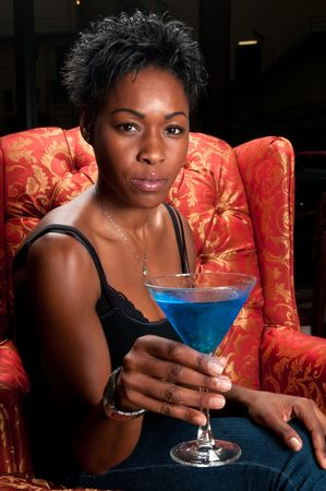 african woman face: Young african american very happy having a blue martini cocktail in a restaurant.