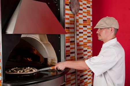 Young hispanic immigrant cooking pizza in a restaurant. Stock Photo