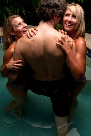 Sexy caucasian girls flirting with young man in a pool.