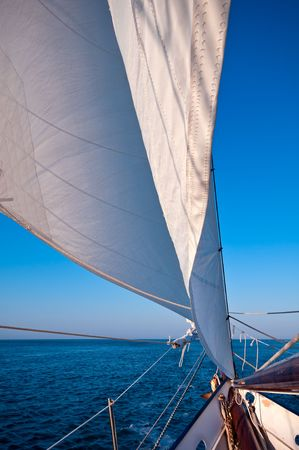 Sailboat navigates in the ocean at sunset time. Space for copy.