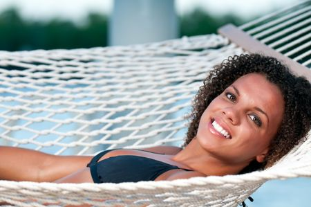 Young woman resting in a hammock with marine background photo