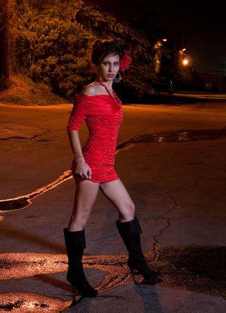 Jonge latino vrouw in een steegje in de nacht. Stockfoto