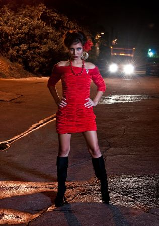 prostitute: Young hispanic woman in a alley at night while a truck is passing by.