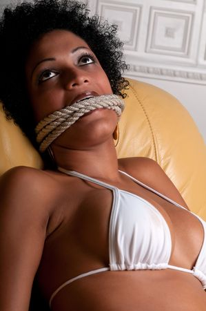 Young brunette woman very scared and bonded with ropes. photo