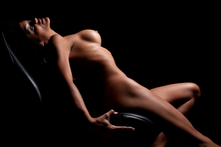 anatomy naked woman: Young brunette posing nude in dim light.