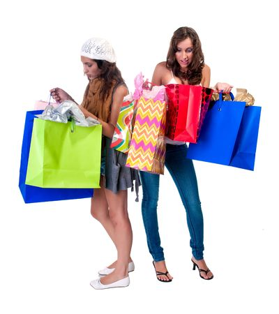 Young caucasian and hispanic girls looking at shopping bags very interested. photo