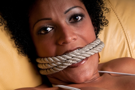 Young brunette woman very scared and bonded with ropes. Stock Photo - 5572486