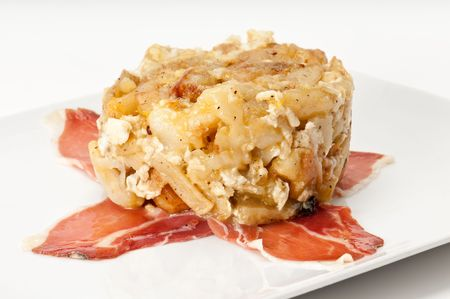 spanish tapas: Close up view of tapa huevos rotos, literally translated as broken eggs, is a Spanish staple dish of potatoes, ham and eggs.
