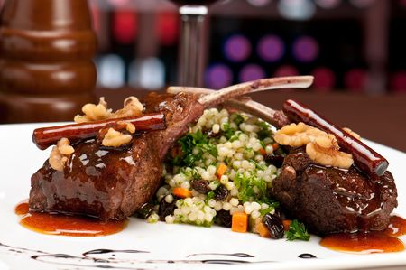 pirzola: Close up of lamb chops with couscous and vegetables with a sauce of caramel, pepper and spices in a restaurant setting. Stok Fotoğraf