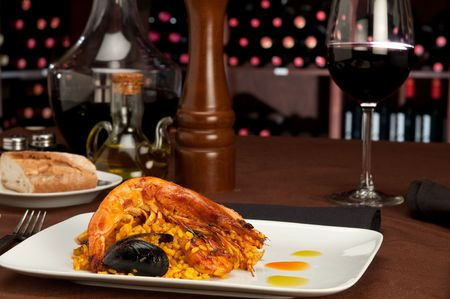 Tradition Seafood Spanish Paella in a restaurant table setting and wine cellar in the background. photo