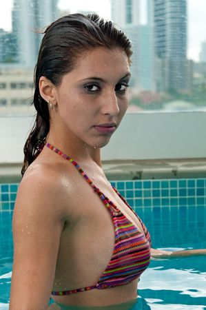 Young hispanic woman enjoys the spa in the terrace of a upscale building. Archivio Fotografico