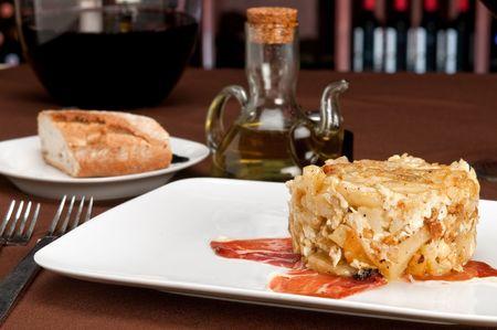 Close up view of tapa huevos rotos, literally translated as Òbroken eggsÓ, is a Spanish staple dish of potatoes, ham and eggs.