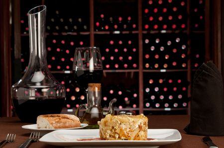 Restaurante tabel instelling met tapa huevos rotos, letterlijk vertaald met �broken eggs�, is een Spaanse stapel schaaltje van aard appelen, ham en eieren. Wijn kelder op de achtergrond Stockfoto
