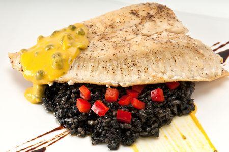 Cierre de la placa de filete de mero sobre un lecho de arroz con tinta de calamar, alcaparras, tomate y mostaza. Foto de archivo - 5572504