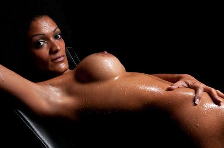 Young hispanic woman pasing nude and wet in dim light.
