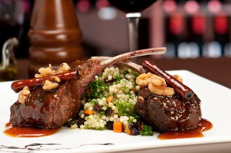 Close up of lamb chops with couscous and vegetables with a sauce of caramel, pepper and spices in a restaurant setting. Banco de Imagens