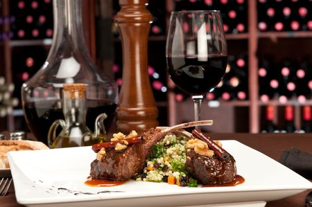 Close up of lamb chops with couscous and vegetables with a sauce of caramel, pepper and spices in a restaurant setting. photo