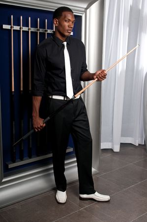 cue sticks: Young professional african american pool player posing with cue, in billiard saloon.