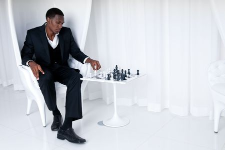 Young African American Playing Chess in a upscale location. photo
