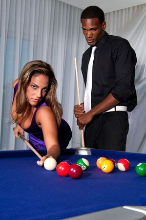 Multiracial couple playing pool at night in upscale place. photo