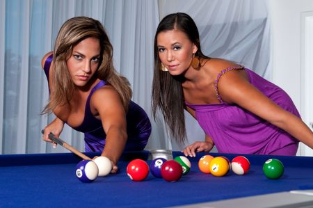 2 young womans playing pool looking at camera very sensual. Stock Photo - 5644959