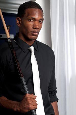Joueur de jeunes pool afro-américains professionnel posant avec cue, au billard saloon.