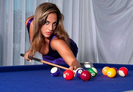 Young hispanic girls plays pool with a very sexy dress. photo