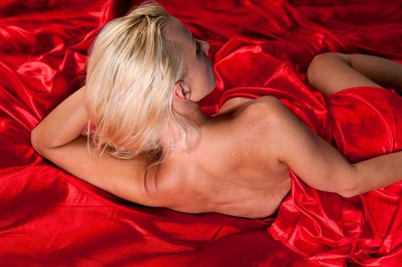Young glamour model posing naked in red silk sheets. Stock Photo - 5697662