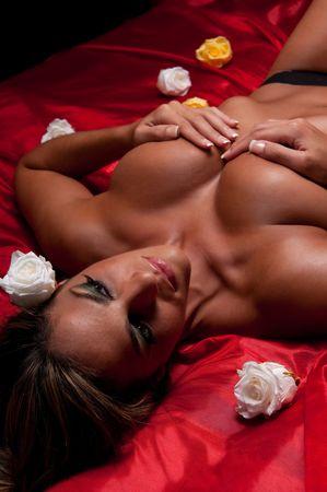 Jonge Spaanse vrouw tot in bed met zijden blad en rozen.