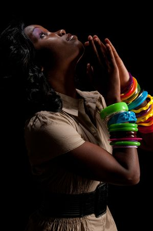 Young african american praying in dim light. photo