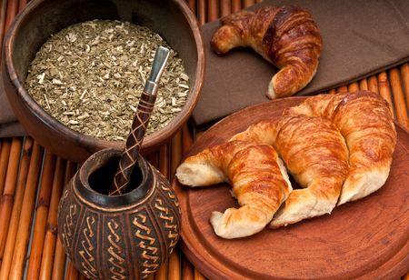yerba mate: Taza de calabaza para mate y croissants, con yerba mate en primer plano. Mate es una tradici�n muy popular en Argentina y Uruguay.  Foto de archivo